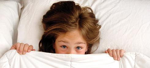 Ein Mädchen schützt sich erfolgreich unter einer kuscheligen Daunendecke