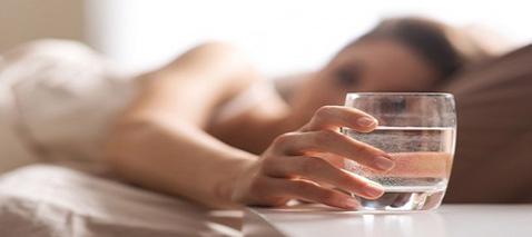 Eine junge Dame liegt im Bett und greift nach einem Glas Wasser auf dem Nachttisch