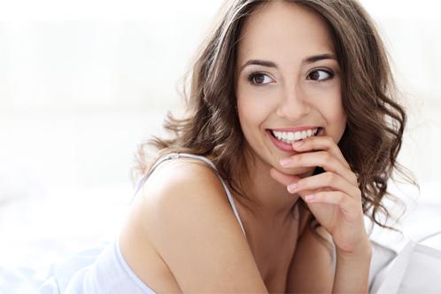 lächelnde Frau mit langen, braunen, lockigen Haaren, liegend auf einem Bett