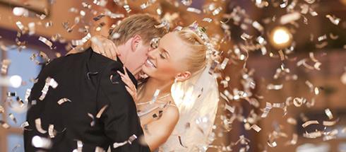 Ein lachendes Brautpaar im Lamettaregen